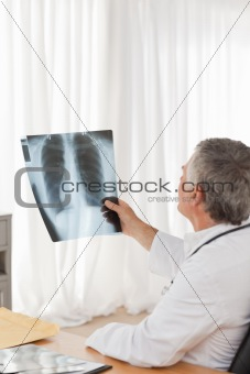 A senior doctor looking at the X-ray