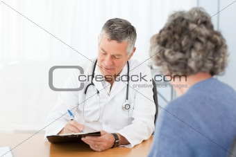 A senior doctor talking with his patient in his office