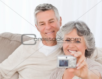 Mature couple taking a photo of themselves at home