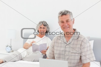 Man working on his laptop while his wife is reading