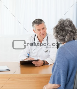 A senior doctor talking with his patient
