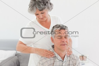 Retired woman giving a massage to her husband at home