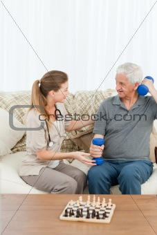 Lovely nurse helping her patient to do exercises