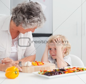 Little boy looking at his grandmother cooking at home