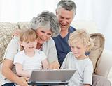 Adorable family looking at the laptop at home