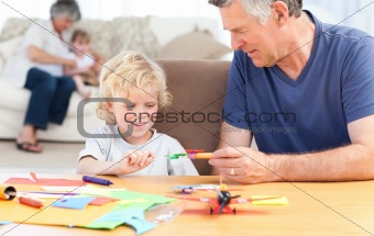 Little boy drawing with his grand father