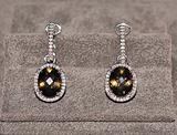 Elegant jewelry earrings with topaz and brilliants over textile