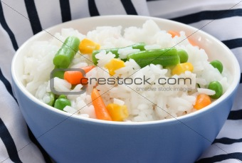 Blue bowl with cooked rice with mixed vegetable