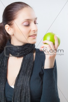 Beautiful young woman holding green apple