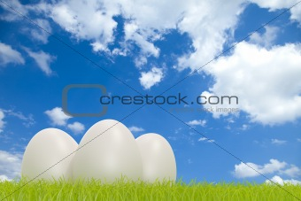 Three white eggs on grass in front of a cloudy sky