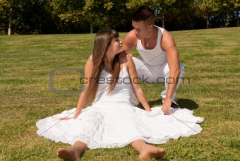 young couple happy sitting on grass white clothes, love relationship