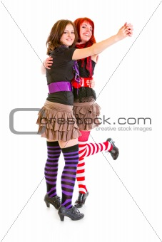 Two cheerful young girlfriends dancing for fun