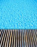 wood floor beside the blue swimming pool