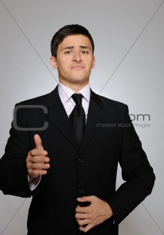 Young serious business man in black suit and tie.