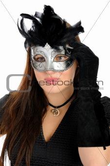 Beautiful brunette woman in black dress in party carnival mask .