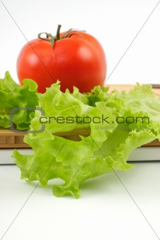 tomato and salad sheet on a wooden board