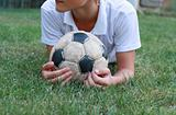 Boy with old soccer ball