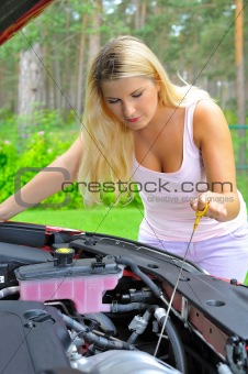 Young woman checking oil level in the car