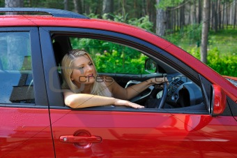beautiful woman driver in red shiny car outdoors smiling