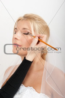 Professional wedding make-up is being applied to beautiful bride