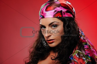 Beautiful gipsy woman with bright make-up. red background