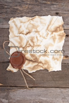 Old paper with a wax seal on wood texture