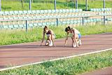 two girls running on athletic race track