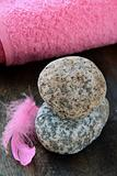 pink feather on the stones and pink towel in the background