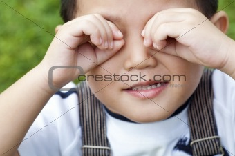 Boy covering eyes