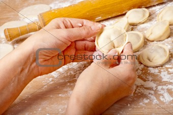 Women's hands are preparing pelmen.