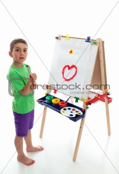 Young child standing at art easel