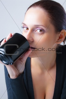 Beautiful young woman drinking from a cup