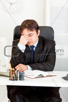 Tired modern businessman sitting at office desk