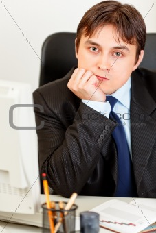 Thoughtful modern businessman sitting at office desk