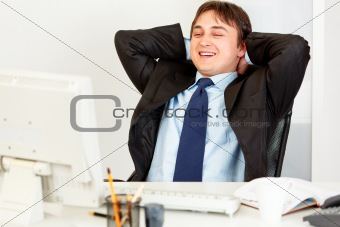 Laughing businessman sitting at office desk and looking at computers monitor