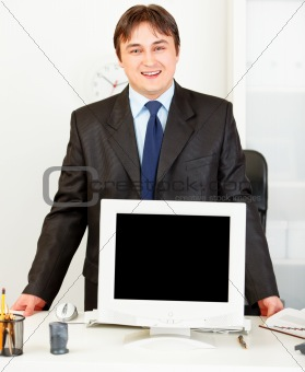 Smiling businessman standing at office desk and showing monitors blank screen