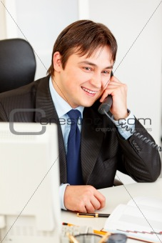 Smiling modern businessman sitting at office desk and talking on phone