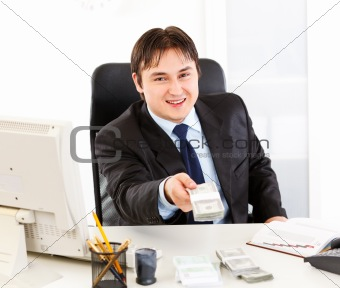 Smiling  businessman sitting at office desk and giving dollar pack