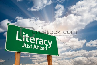 Literacy Green Road Sign with Dramatic Clouds, Sun Rays and Sky.