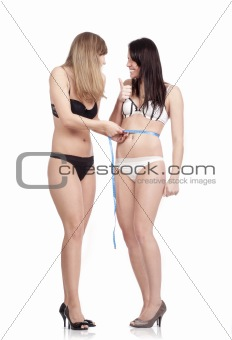 two young women in underwear measuring results of diet - isolated on white