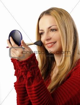 Beautiful woman applying blush