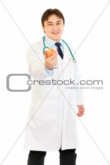 Smiling  medical doctor holding apple