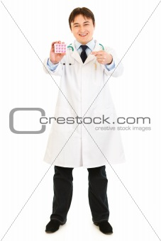 Smiling  medical doctor pointing finger on pack of pills