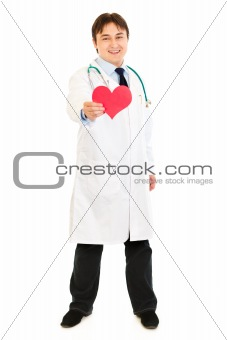 Smiling medical doctor holding paper heart in hand