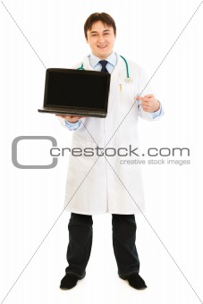 Smiling  doctor pointing finger on  laptop with blank screen