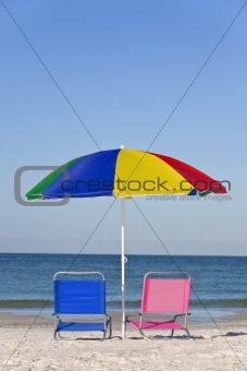 Colorful Beach Umbrella with Pink and Blue Deckchairs