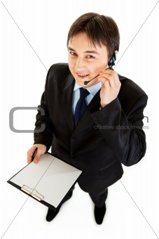 Smiling young businessman with headset holding clipboard