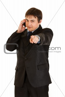 Smiling businessman talking on mobile and showing contact me gesture