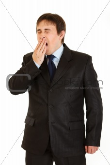 Tired young  businessman yawning