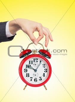 an alarm clock in woman hand over yellow background